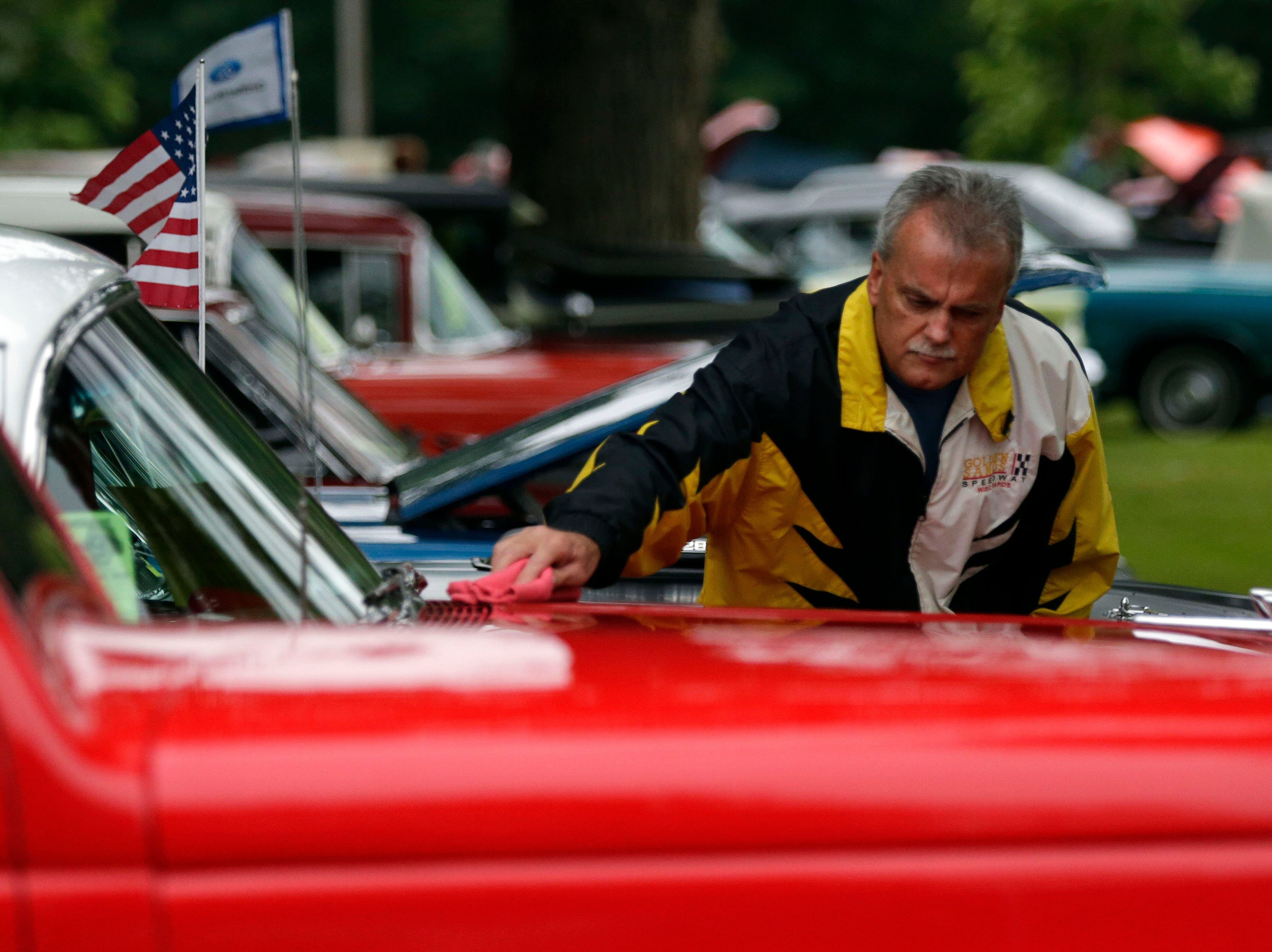 Brian Gulke cleans his car after driving from Custer, Wis., to the Appleton Old Car Show and Swap Meet Sunday, July 22, 2018, at Pierce Park in Appleton, Wis.