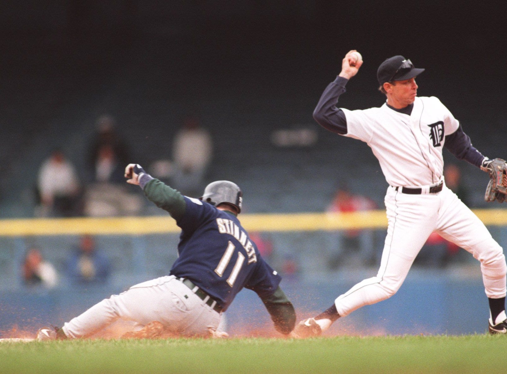 Trammell throws to first base as #11 Kelly Stinnett slides into second in 1996.