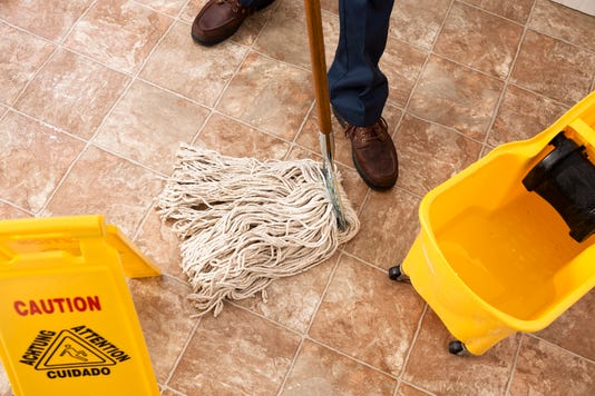 Caution Sign Janitor Man Mopping Floor Of Retail Store Cleaning