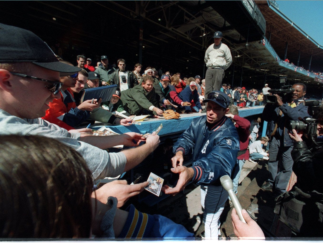 Alan Trammell sings autographs for fan who arrived at the stadium early to see members of the 1984 championship team before the last season opener at Tiger Stadium.