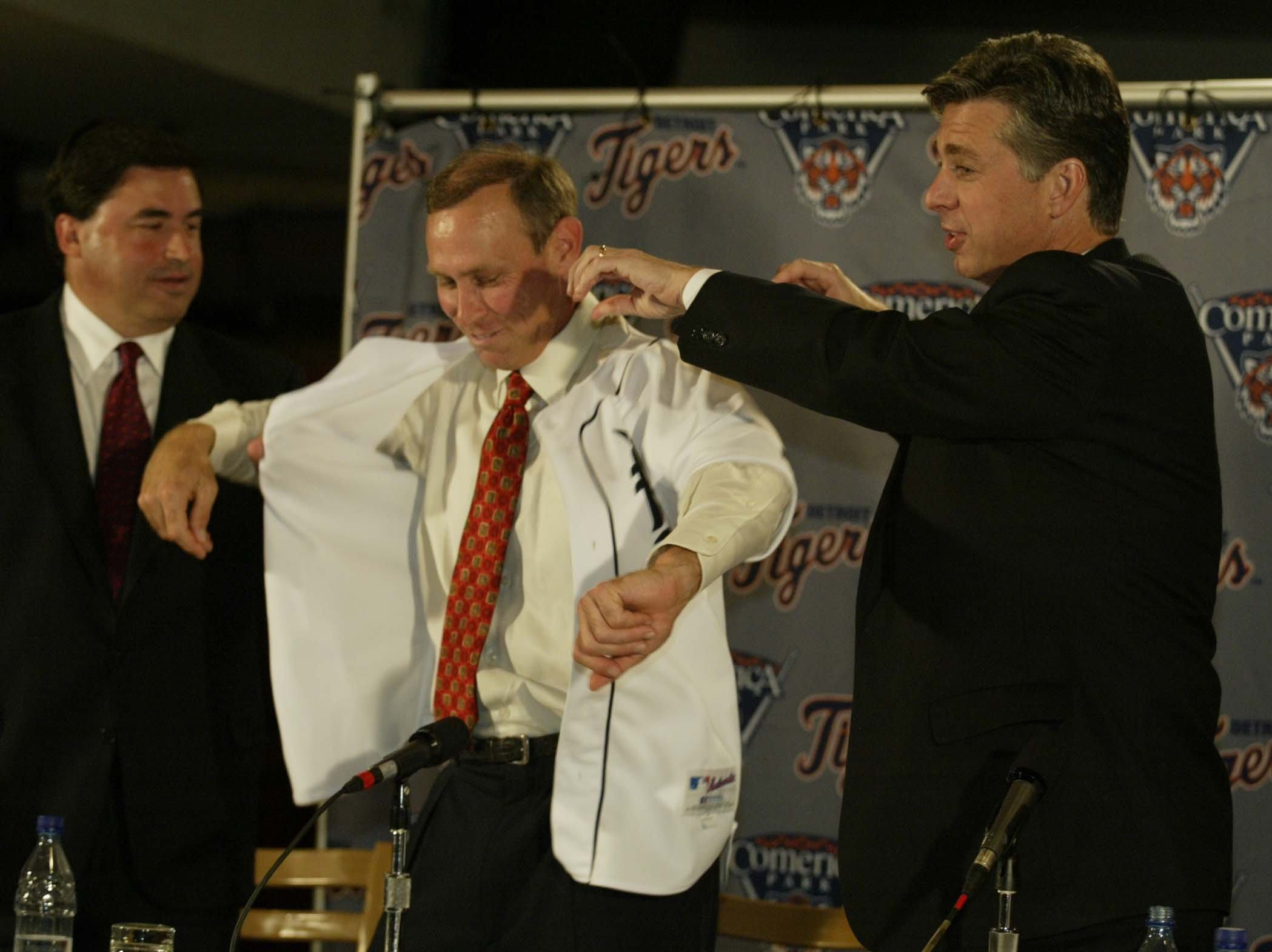Alan Trammell gets a helping hand with his jersey from Tigers general manager Dave Dombrowski during a press conference to announce Trammell as the new Detroit Tigers manager while at Joe Louis Arena on Wednesday, October 9, 2002.