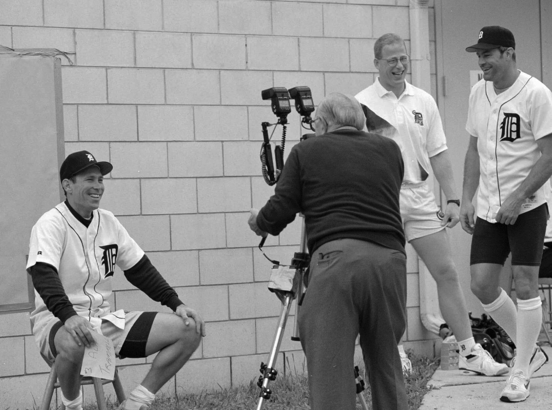 """Detroit Tigers' Alan Trammell, seated, poses for a portrait for Tigers team photographer Drayton """"Doc"""" Holcomb, as Brad Andress, Tigers strength and conditioning coach and Kirk Gibson, right, wait in line, during team picture day at spring training in Lakeland, Fla., Friday, Feb. 25, 1994."""