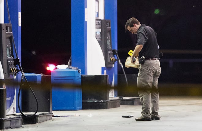 A Fort Myers Police department official marks a gun with an evidence marker on Saturday at the Marathon gas station on Dr. Martin Luther King Jr. Boulevard in Fort Myers. A Fort Myers Police officer was shot near the station and is being treated at Lee Memorial Hospital.