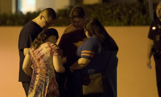 People pray outside Lee Memorial Hospital on Saturday, July 21, 2018, in Fort Myers. A Fort Myers police officer was shot earlier in the night.