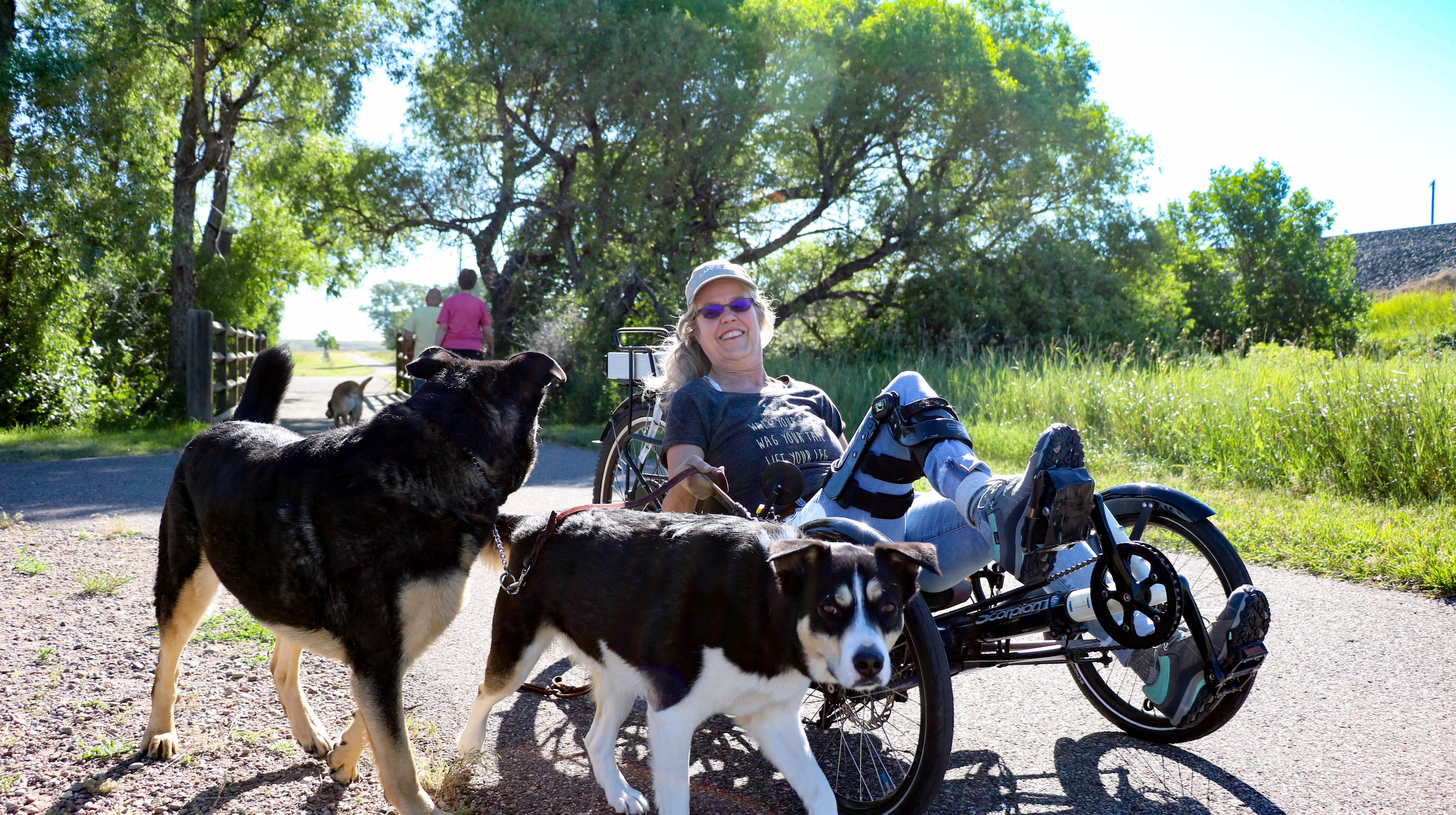 Grayce Holzheimer rides her motorized tricycle, along with her dogs Echo and Sport, on the River's Edge Trail in Great Falls. Great Falls College MSU student Ilaya Payne motorized the tricycle as part of a research project.