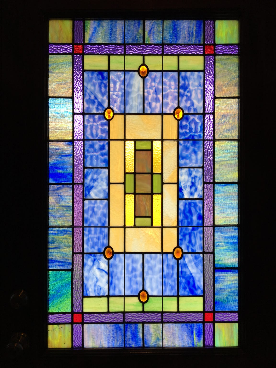 Stained glass, photographed July 19, 2018, adorns the doors of the funeral home in Winona where Lola Flowers' body awaits her funeral. Flowers passed away on July 14, 2018. Her son Curtis Flowers is on death row, having been tried six times for the July 1996 quadruple murders at Tardy Furniture in Winona.