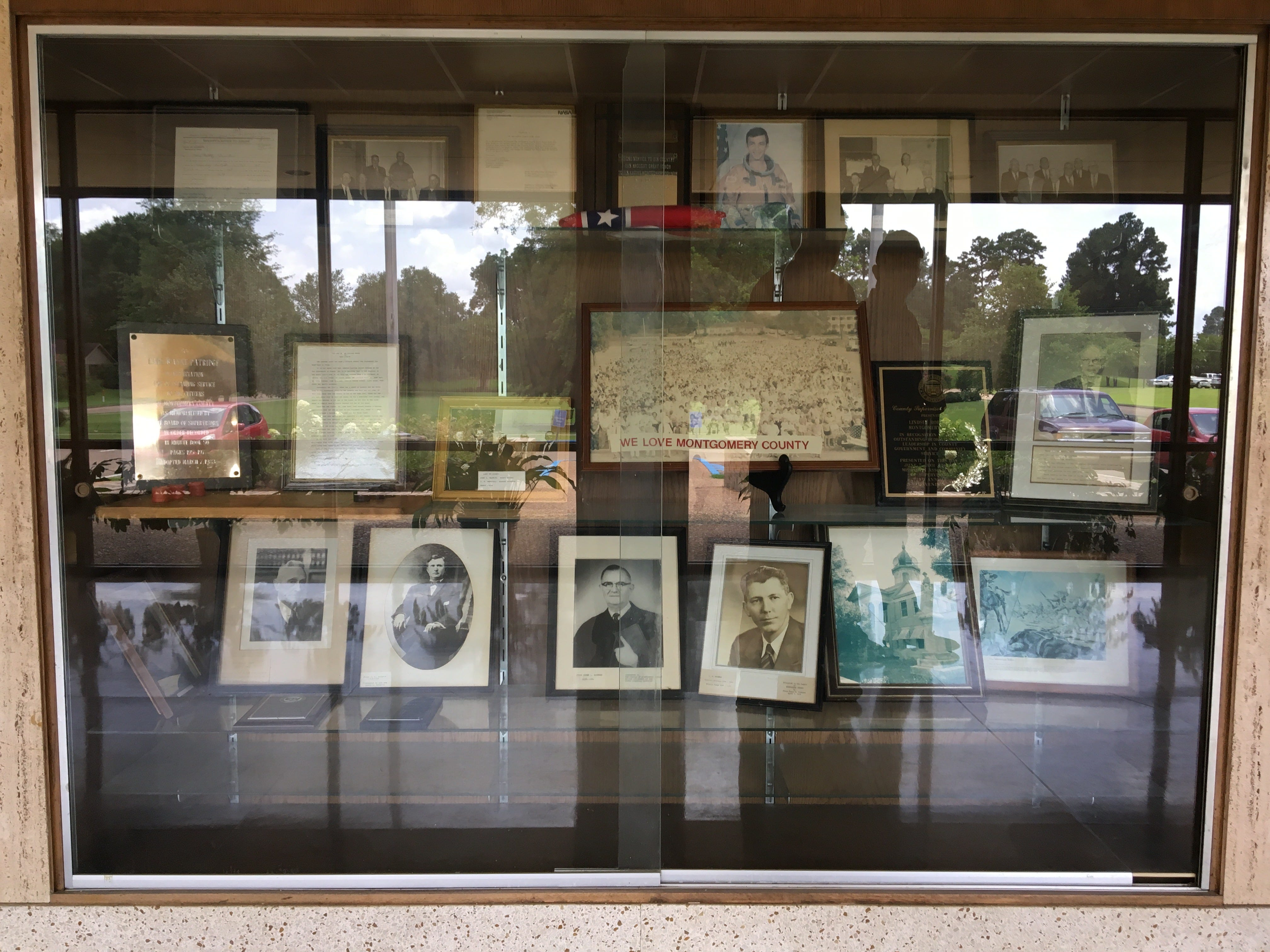 A cabinet in the lobby of the Montgomery County Courthouse displays a folded confederate flag, images and memorabilia of dignitaries from the county and Winona, MS. Thursday, July 19, 2018.