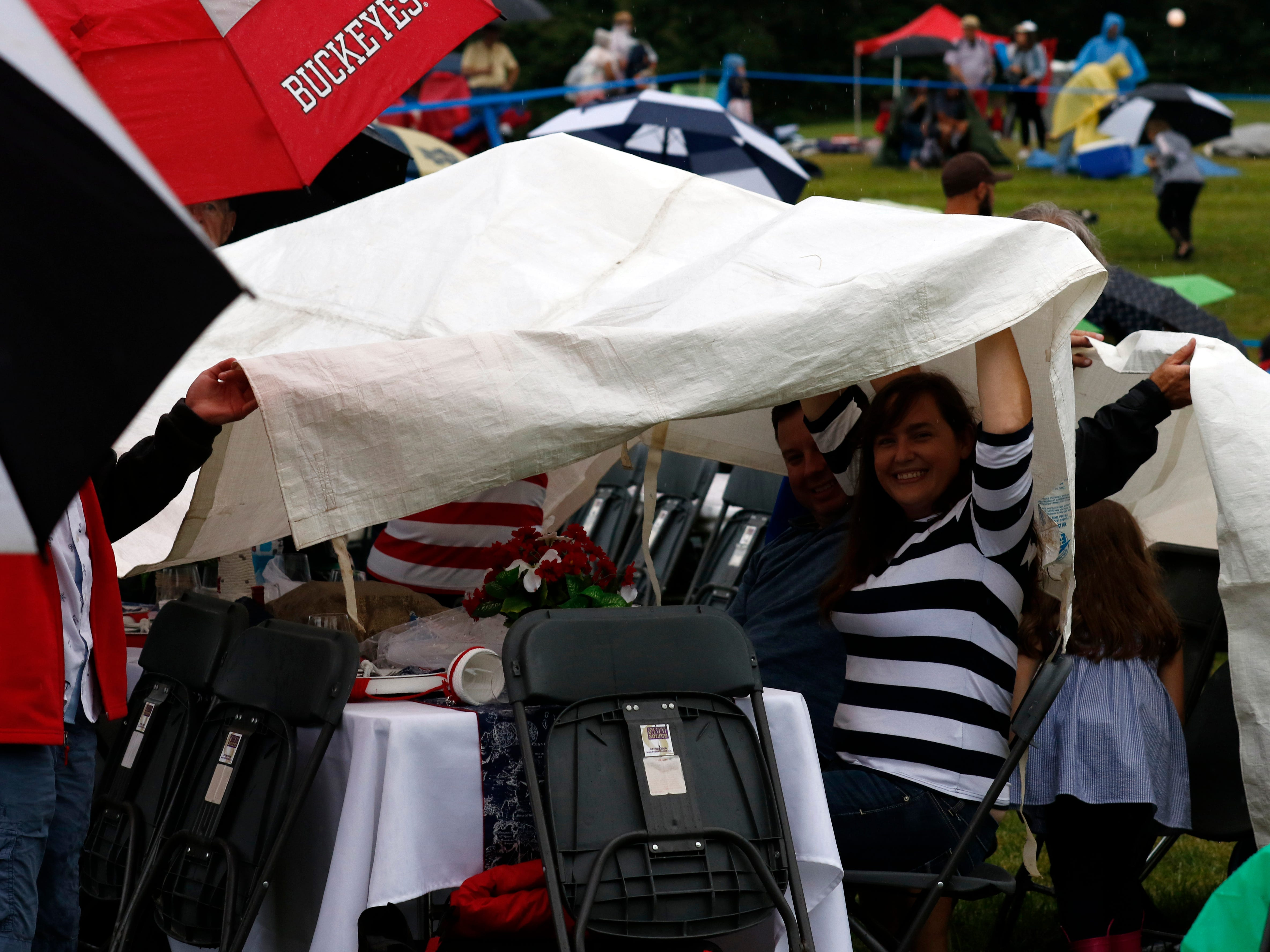 People waited under umbrellas for the beginning of the first headline concert of the 2018 Lancaster Festival. Lightning caused the concert venue to be evacuated about an hour before the concert was scheduled to start. Fairfield County Sheriff's Office Lt. Marc Churchill said hundreds of concert goers were cleared from the in less than 20 minutes. He said about half of the people sought shelter at Ohio University Lancaster, while the rest went to their cars.