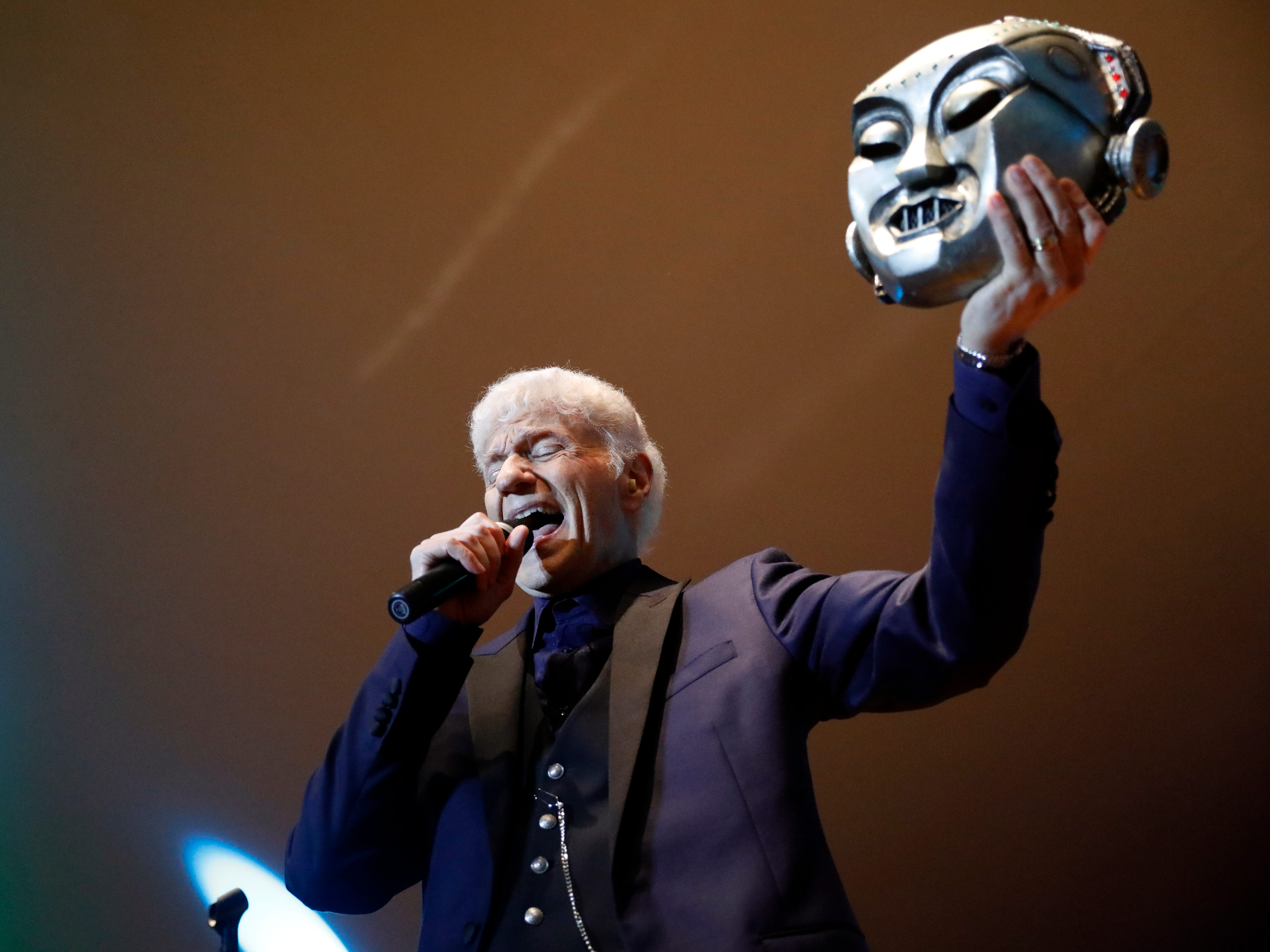 """Dennis DeYoung holds up a Kilroy mask as he sings """"Mr. Roboto"""" during a concert Saturday night, July 21, 2018, at the Ohio University Lancaster Wendel Concert Stage in Lancaster. DeYoung performed the first headline concert of the 2018 Lancaster Festival."""