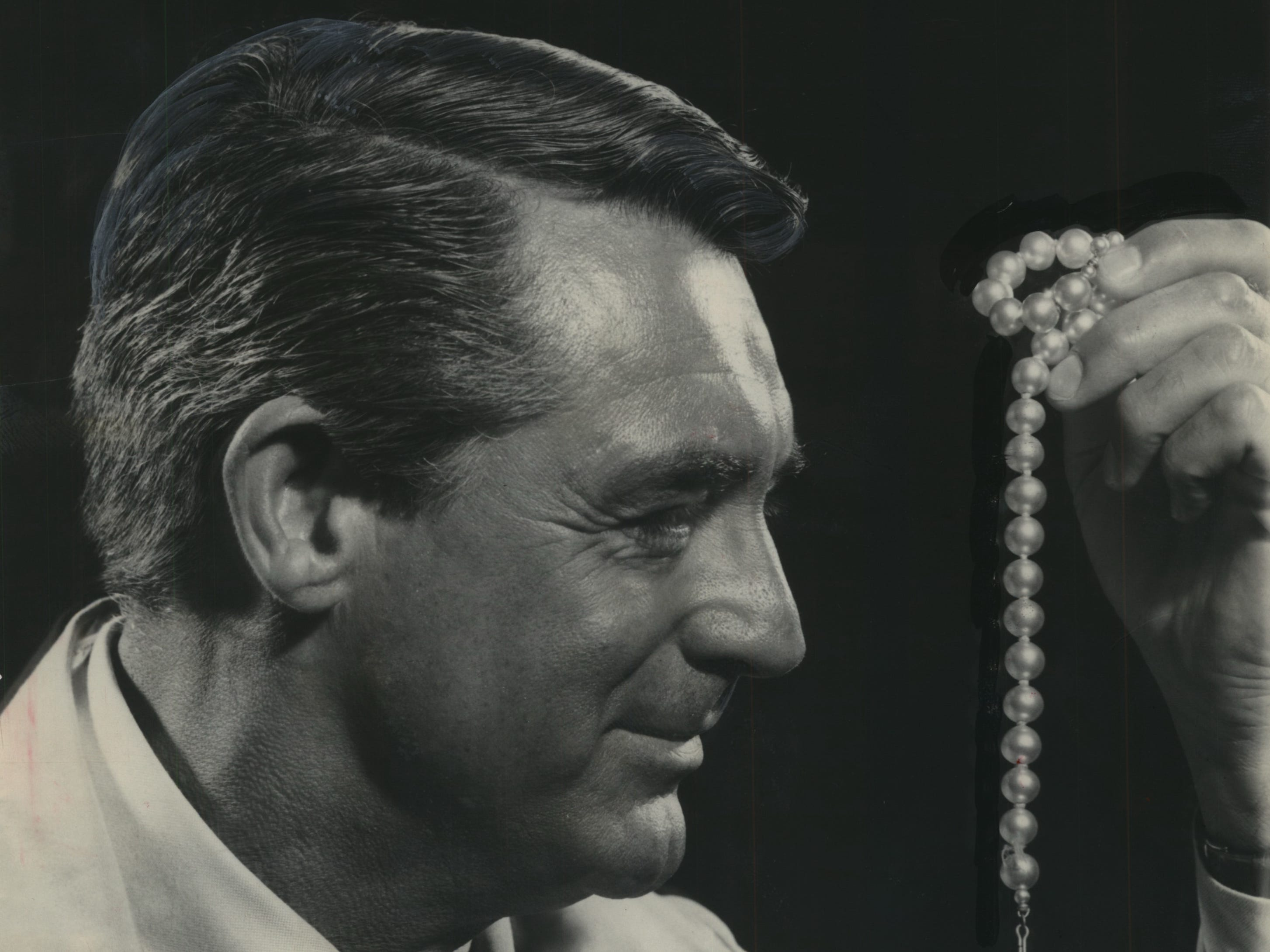 "Cary Grant shows he has an eye for jewels during a visit to Milwaukee on Aug. 19, 1955, to promote his latest movie, the Alfred Hitchcock comic thriller ""To Catch a Thief."" He was scheduled to make two appearances that day at the Riverside Theater, which was showing the movie. This photo was published in the Aug. 19, 1955, Milwaukee Journal."
