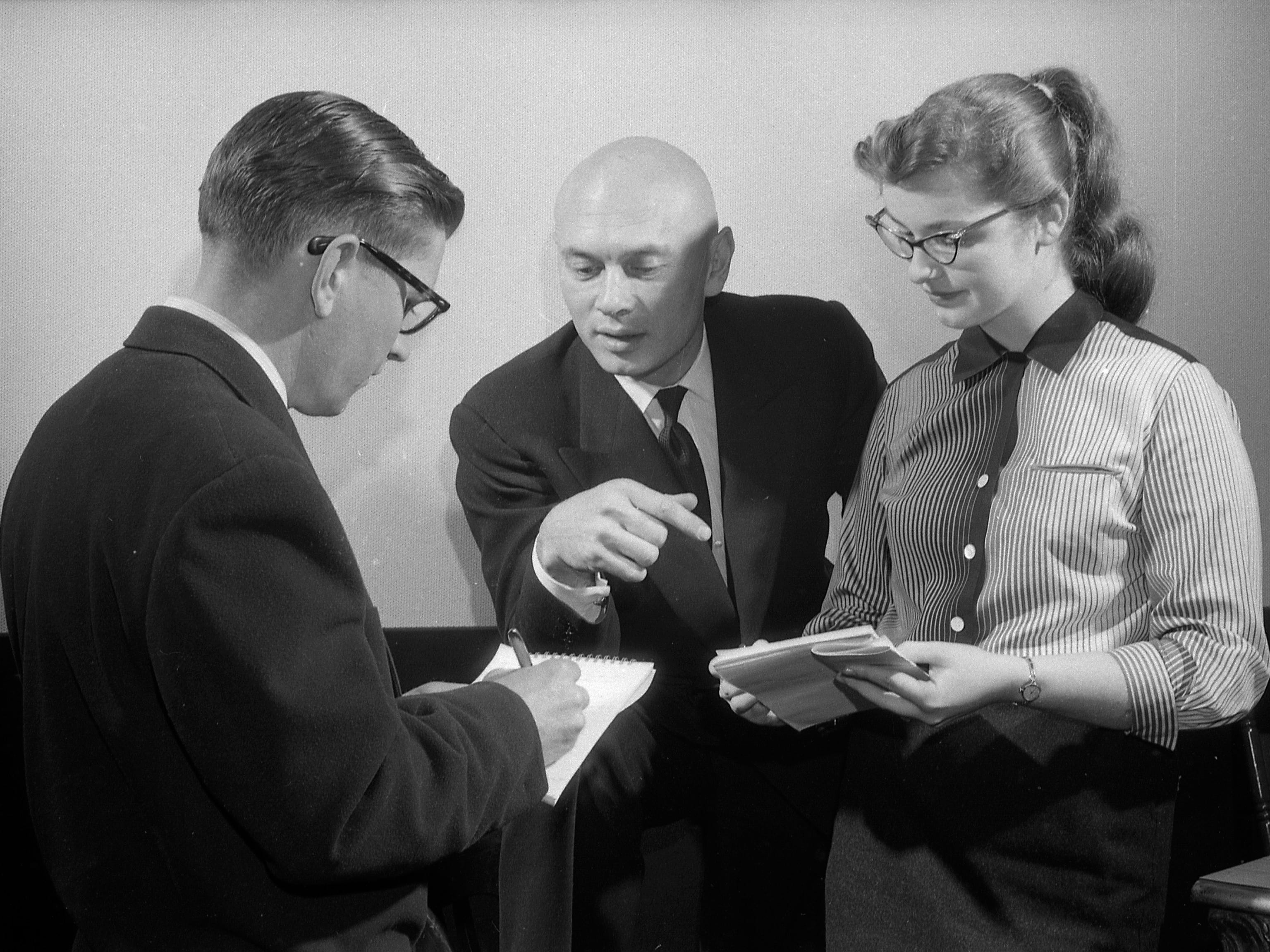"Yul Brynner (center) talks with student journalist Gilbert Molkowski (left) and Margaret Pleister at Milwaukee's Warner Theatre on Feb. 11, 1957. Brynner, in town to promote ""The Ten Commandments,"" also spoke at a crime-prevention rally at Marquette University, and a dedication of a monument to the Ten Commandments in Milwaukee. This photo was published in the Feb. 12, 1957, Milwaukee Journal."