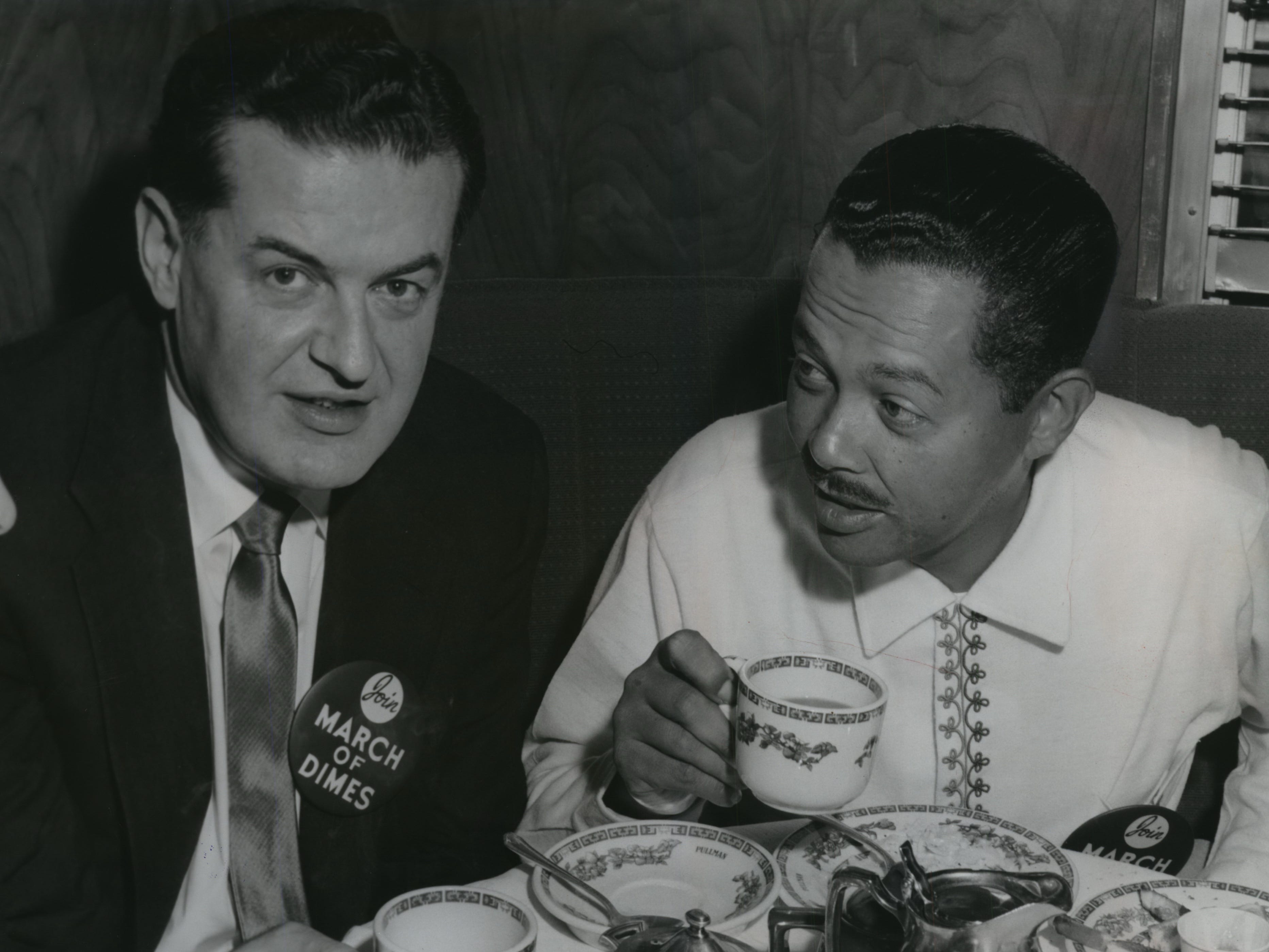 Crooner Billy Eckstine (right) and bandleader Hugo Winterhalter take break during a stop in Milwaukee for a March of Dimes fundraising drive on Jan. 15, 1956.