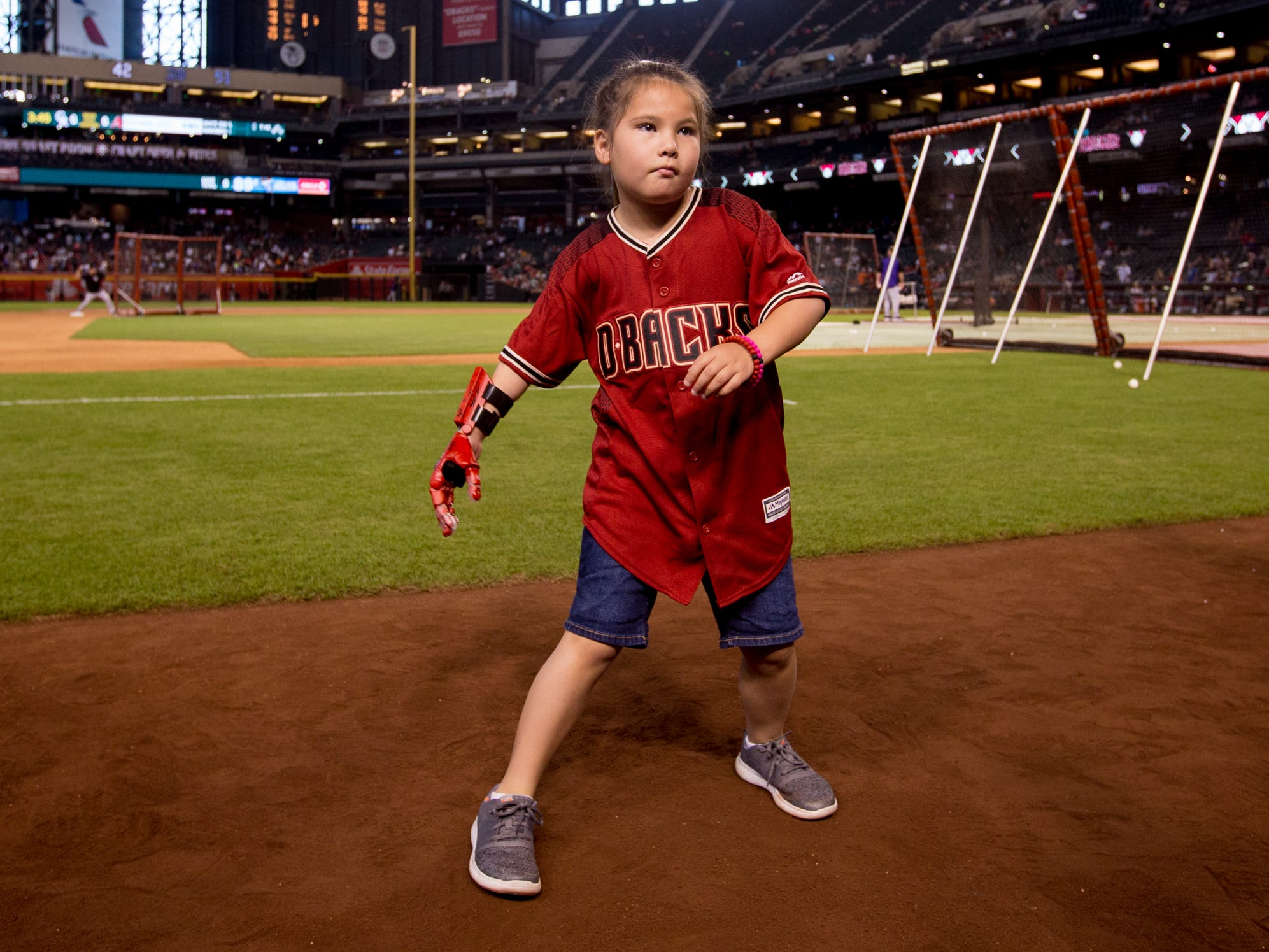 Hailey Dawson, 8, of Henderson, Nevada, dances while waiting to throw the ceremonial first pitch on July 21, 2018, before the Arizona Diamondbacks' matchup against the Colorado Rockies at Chase Field in Phoenix, Arizona. Hailey, born with Poland Syndrome, received a 3D-printed prosthetic hand created by engineering students from the University of Nevada Las Vegas.