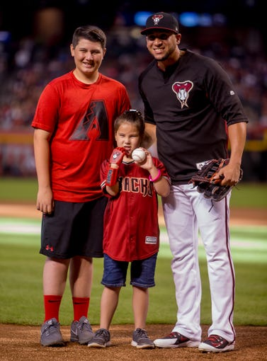 Hailey Dawson (center), 8, poses for a portrait with her brother Zach Henderson, 11, and Diamondbacks center fielder Jon Jay (right) on July 21, 2018, before the Arizona Diamondbacks' matchup against the Colorado Rockies at Chase Field in Phoenix, Arizona.