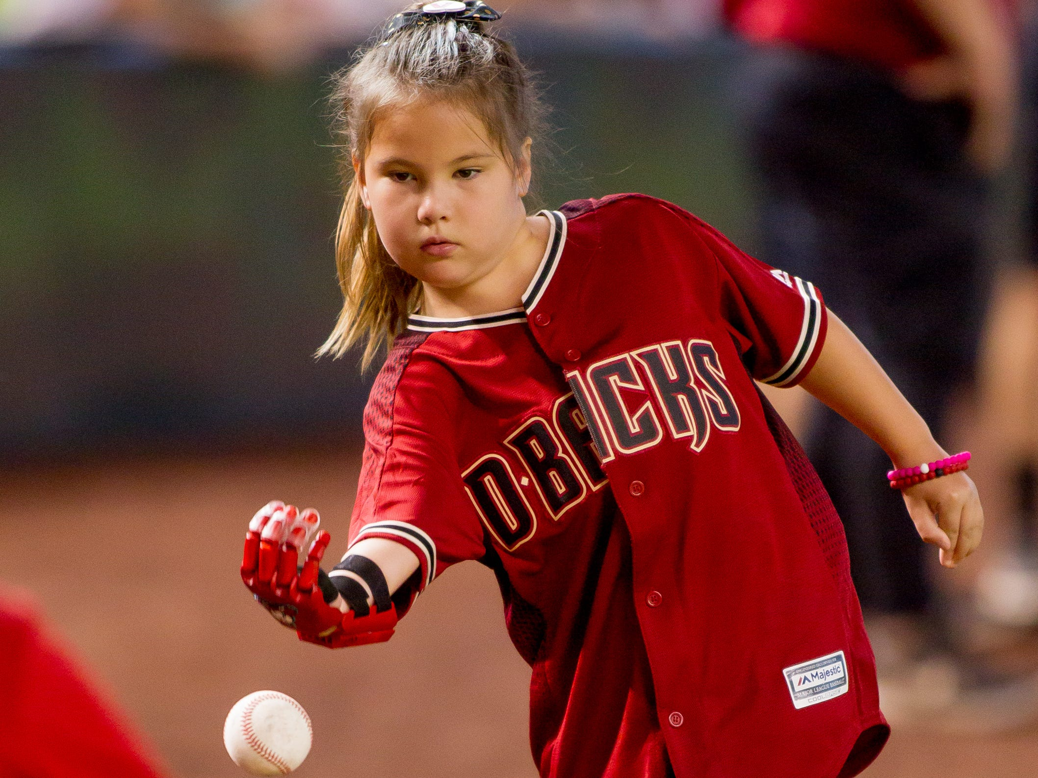 Hailey Dawson, 8, of Henderson, Nevada, practices throwing on July 21, 2018, before the Arizona Diamondbacks' matchup against the Colorado Rockies at Chase Field in Phoenix, Arizona. Hailey, born with Poland Syndrome, received a 3D-printed prosthetic hand created by engineering students from the University of Nevada Las Vegas.
