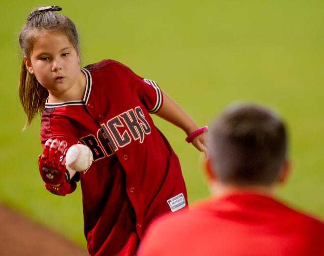 Hailey Dawson, 8, of Henderson, Nevada, practices throwing on July 21, 2018, before the Arizona Diamondbacks' matchup against the Colorado Rockies at Chase Field in Phoenix, Arizona. Hailey, born with Poland Syndrome, received a 3D printed prosthetic hand created by engineering students from the University of Nevada Las Vegas.