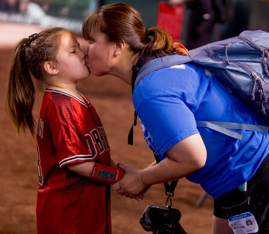 Hailey Dawson, 8, of Henderson, Nevada, kisses her mother Yong Dawson before throwing the ceremonial first pitch on July 21, 2018, before the Arizona Diamondbacks' matchup against the Colorado Rockies at Chase Field in Phoenix, Arizona.
