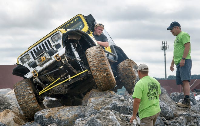 Seth Fike of Willistown works with trail spotters navigating the boulders in a 1976 Jeep CJ5 during the 23rd Annual PA Jeeps All Breeds Jeep Show at the York Expo Center on Sunday.