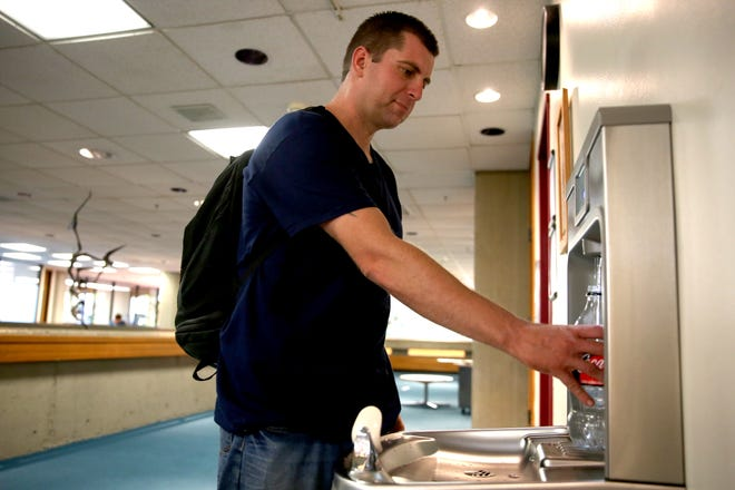 """Daniel Gordon, 33, of Salem, fills up his water bottle at the main branch of the Salem Public Library on Sunday, July 22, 2018. With a heat advisory issued Monday through Tuesday, the city of Salem offers cooling centers at the Salem Public Library or Center 50+. """"I'm here just kind of charging my phone and get out of the heat,"""" Gordon said. """"It's hot out there."""""""