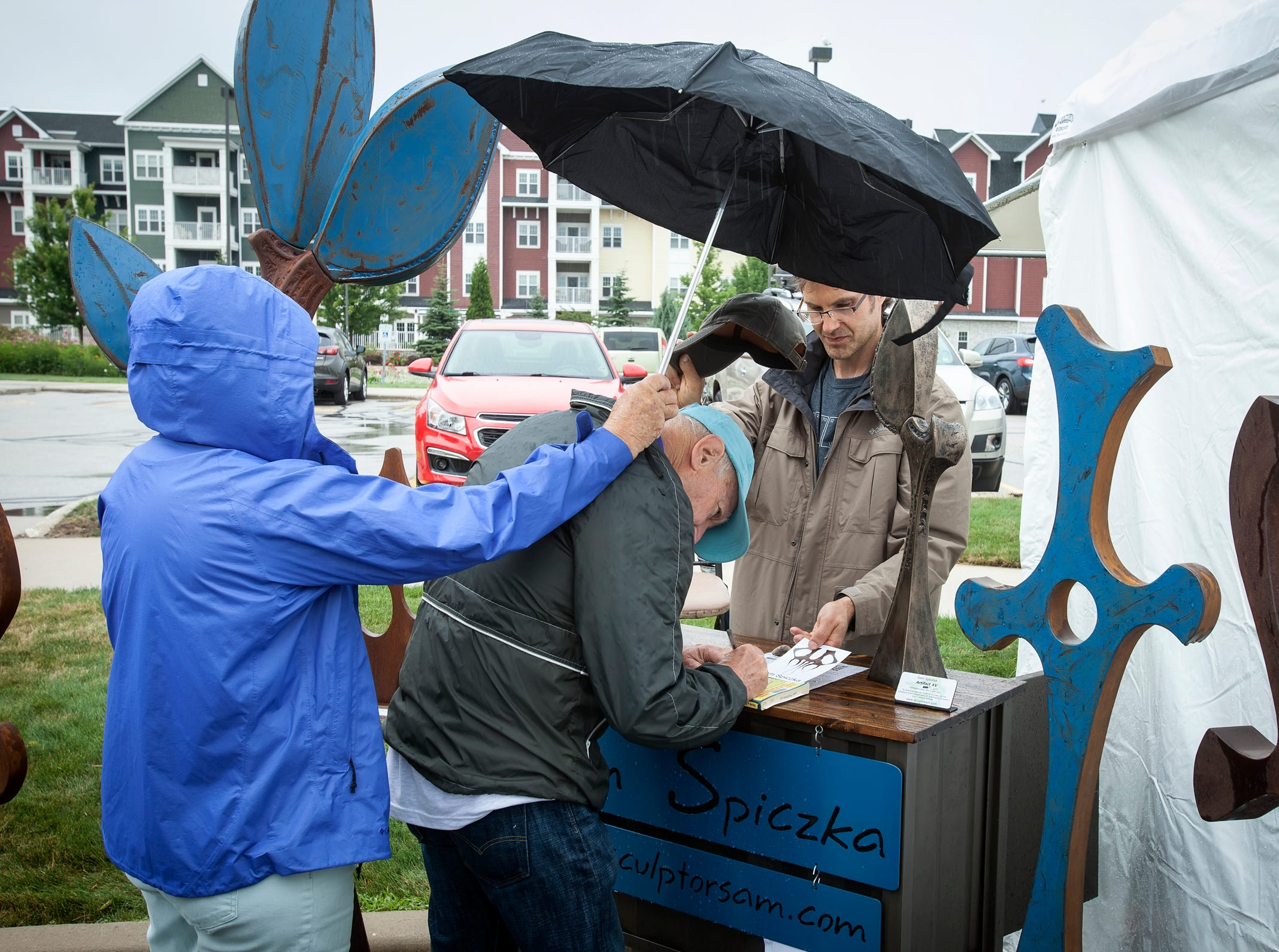 A purchase in the rain from sculptor Sam Spiczka at the Midsummer Festival of the Arts outside the John Michael Kohler Arts Center in Sheboygan on July 21.