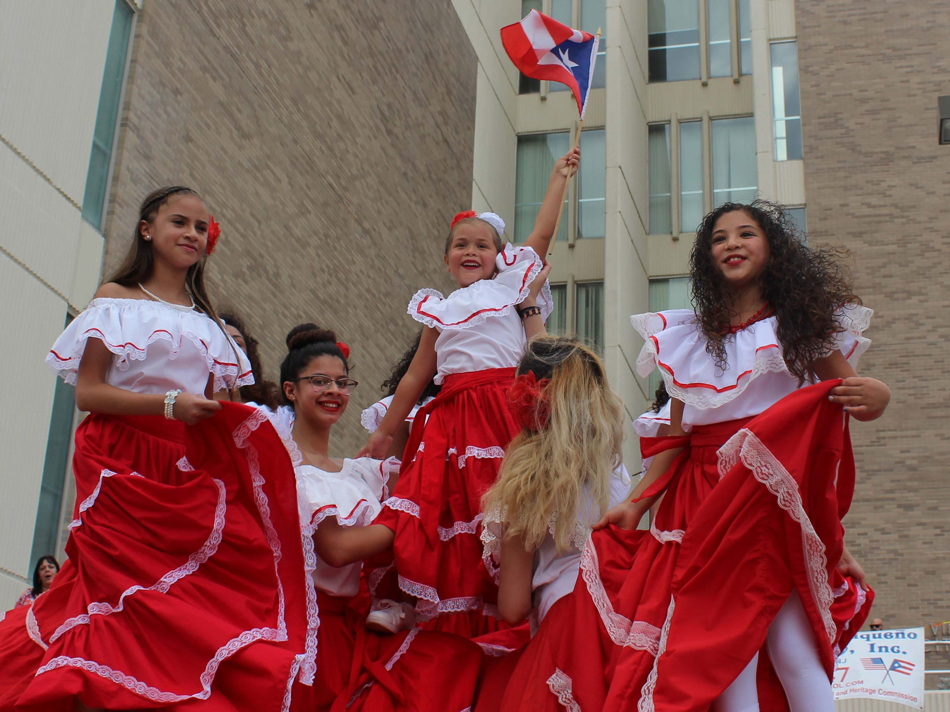 A young dancer proudly raises the Puerto Rican flag to thunderous applause after a dance performance at Vineland City Hall as the Puerto Rican Festival of New Jersey kicked off its 51st annual celebration on Sunday, July 22, 2018.