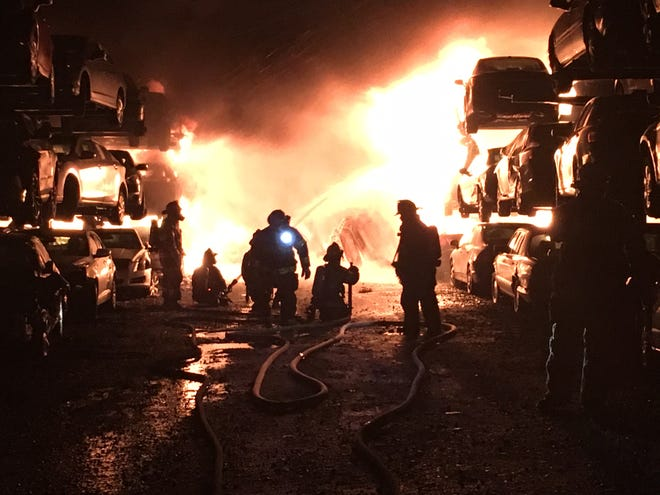Firefighters battle a fire at an auto salvage yard on Old Airport Road near Newport that has engulfed multiple vehicles Saturday evening.