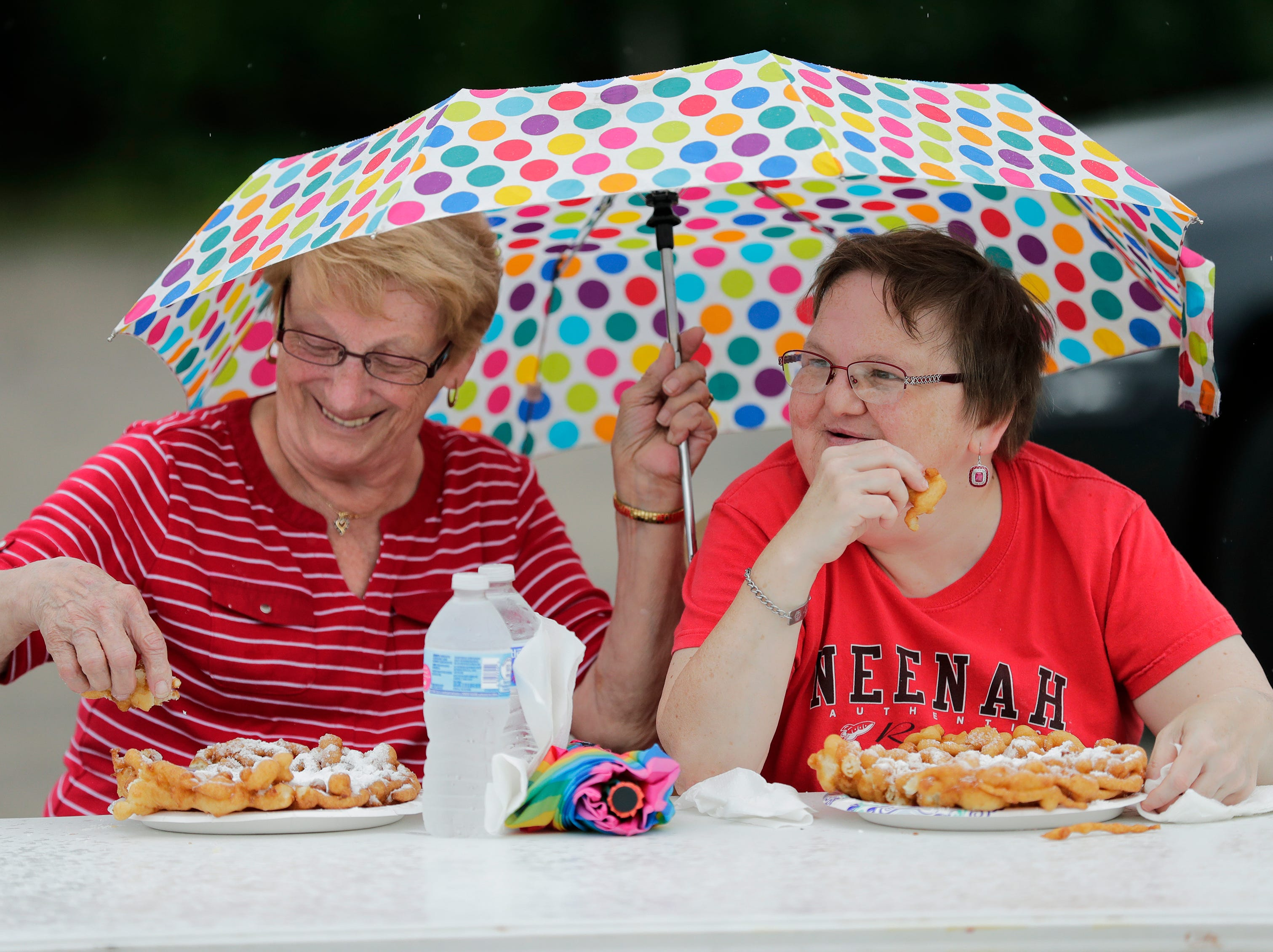 Jane Mrotek, left, and her daughter Laura Mrotek of Neenah eat funnel cake together as they escape the rain during Bazaar After Dark Thursday, July 19, 2018, in Neenah, Wis. The event is hosted Pulse Young Professionals Network at the Fox Cities Chamber.