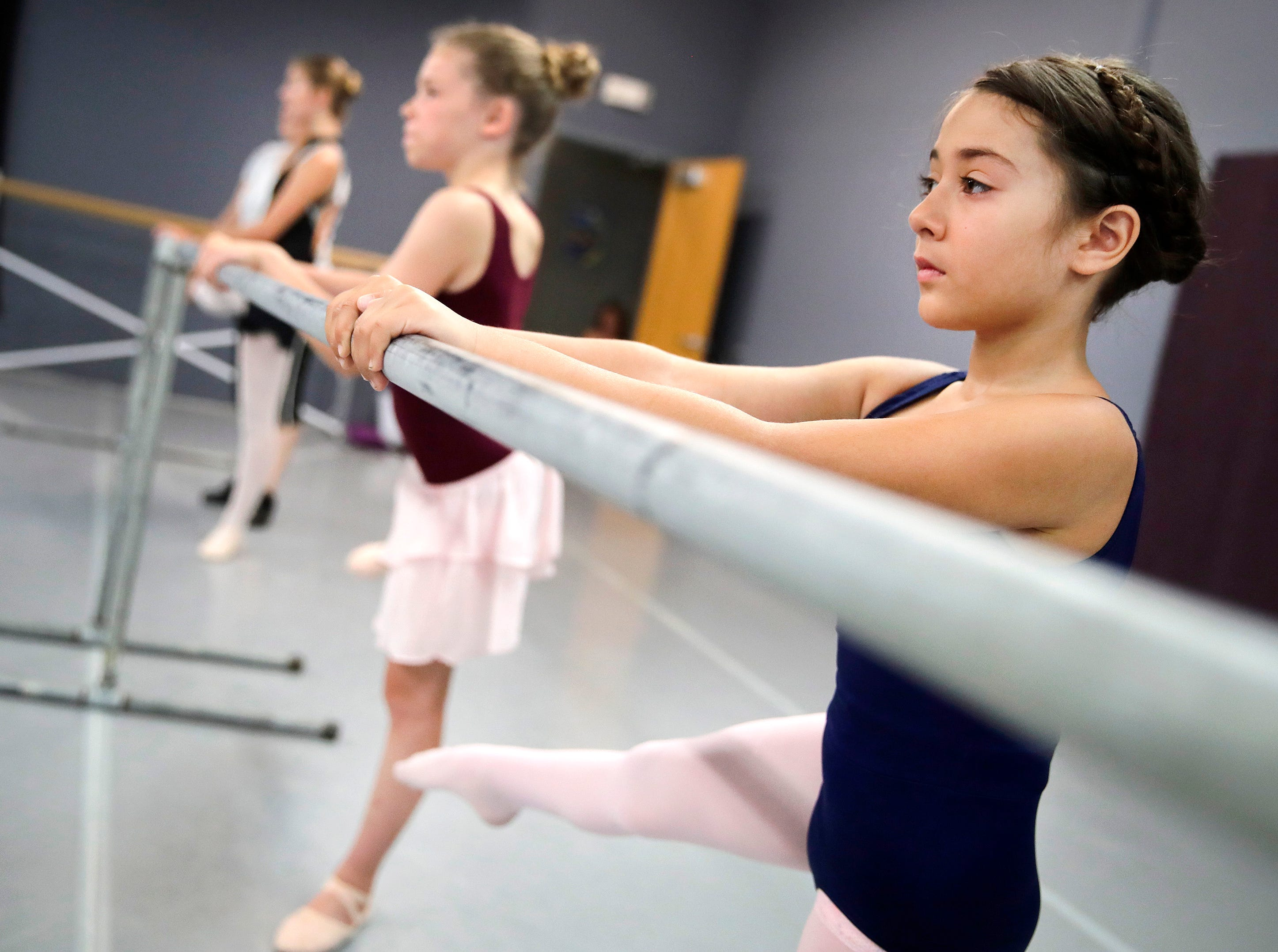 Satya Young-Hofkens, 8, of Appleton, Kaylyn Miller, 9, of Neenah, and Lydia Van boxtel, 14, of Menasha, participate in a beginning ballet class at Valley Academy for the Arts Tuesday, July 17, 2018, in Neenah, Wis. 