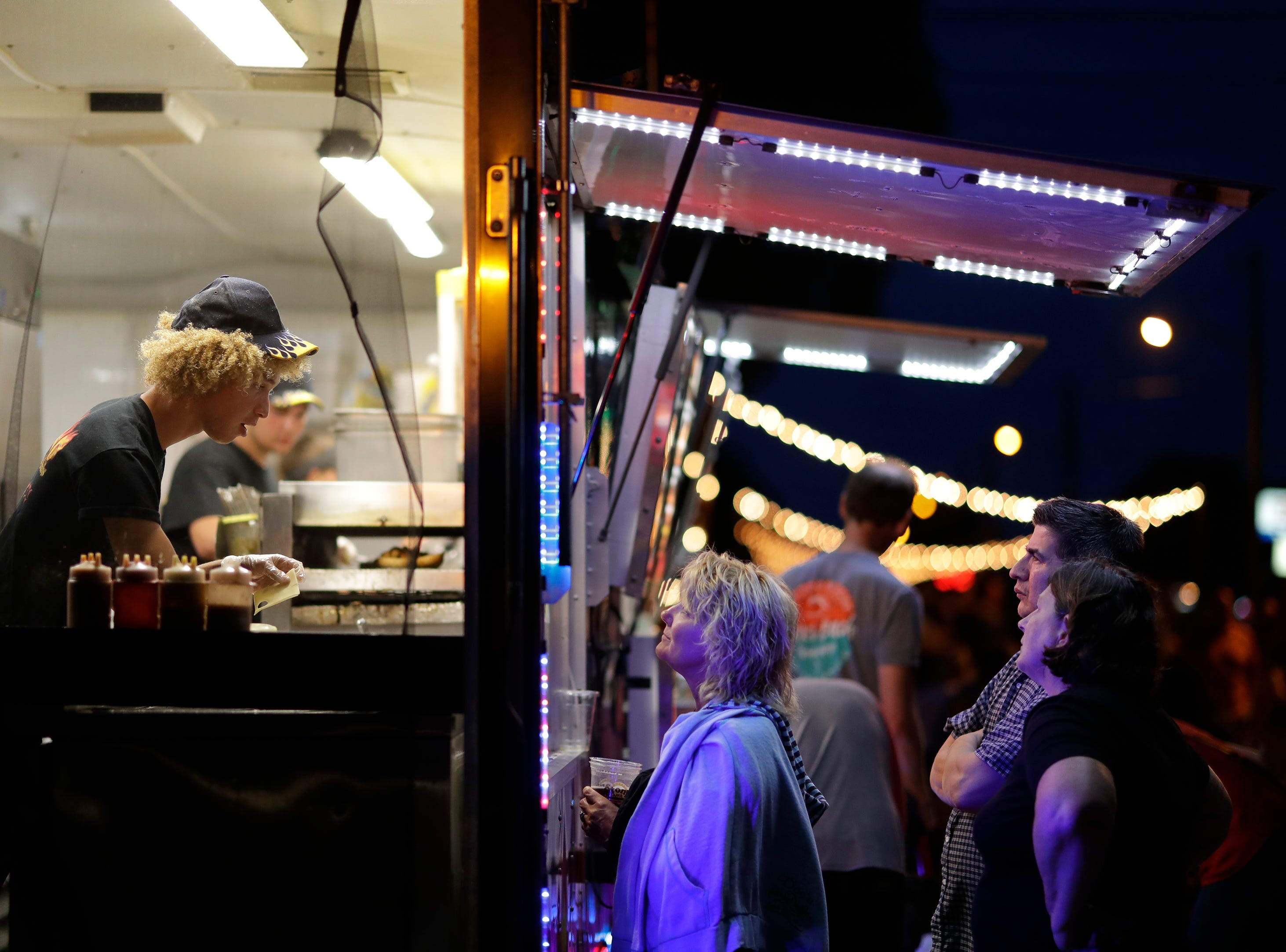 Inferno Gourmet Toasted Subs employee Carston Chancellor, left, of Neenah takes customers orders during Bazaar After Dark Thursday, July 19, 2018, in Neenah, Wis. The event is hosted Pulse Young Professionals Network at the Fox Cities Chamber.