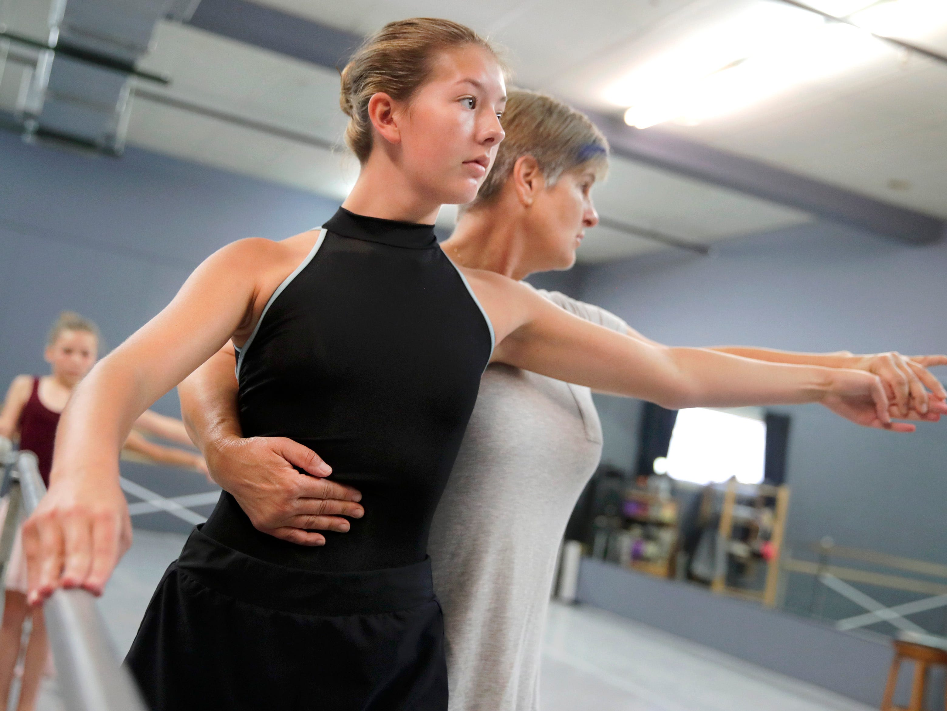 Anne Marie Aberholden, executive director of Valley Academy for the Arts, helps Lydia Van boxtel, 14, of Menasha, with her posture and hand position in a beginner ballet class at the academy Tuesday, July 17, 2018, in Neenah, Wis. 