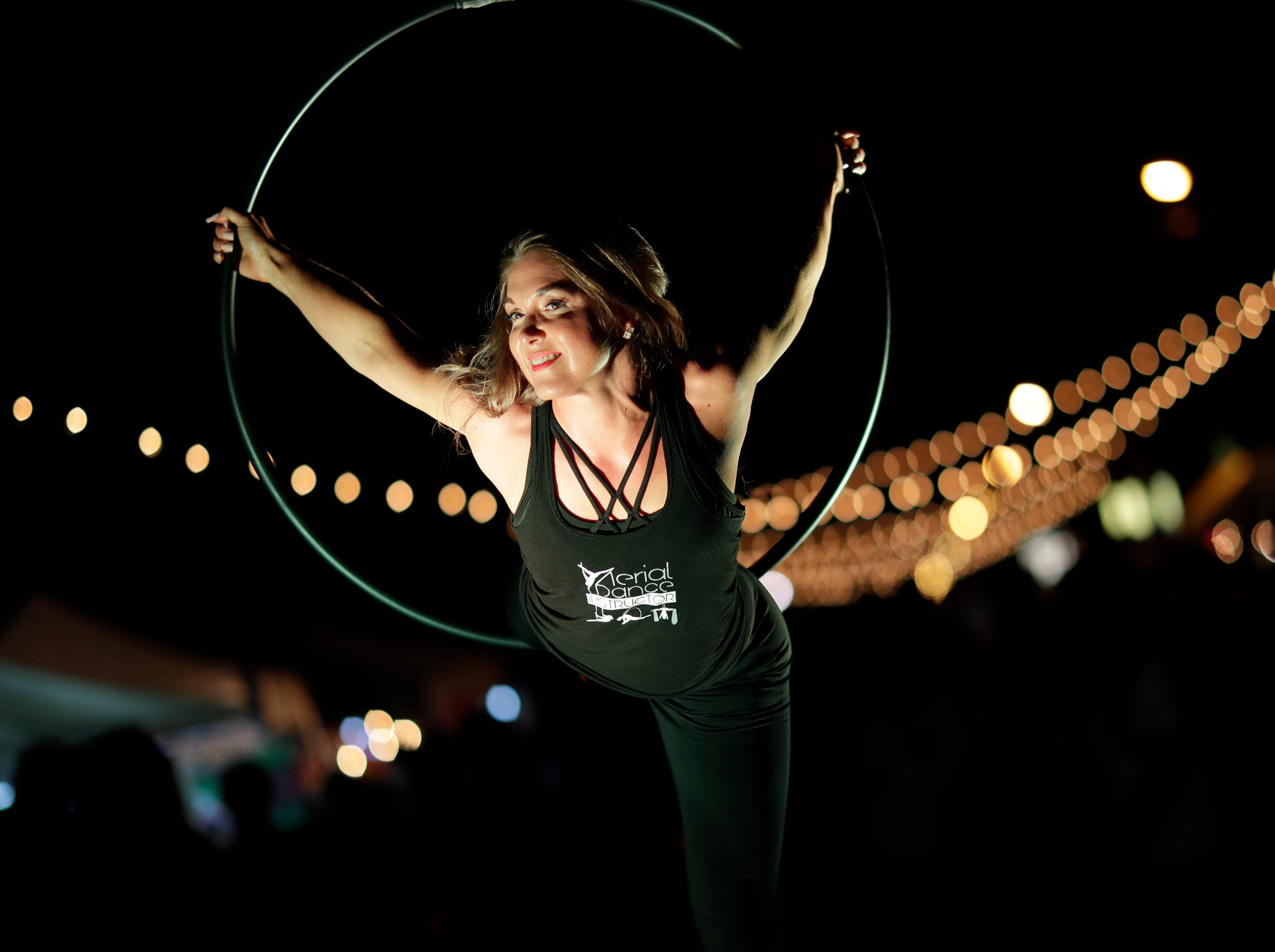 Lynn Stankowski of Appleton performs during Bazaar After Dark Thursday, July 19, 2018, in Neenah, Wis. The event is hosted Pulse Young Professionals Network at the Fox Cities Chamber. Stankowski is with Aerial Dance Pole Excercise.