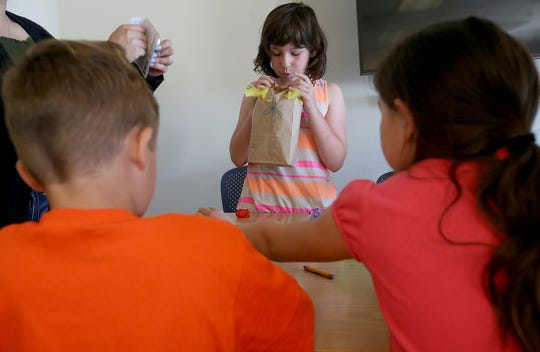 Sahda Walker, 9, blows into a paper bag to inflate it while making a paper bag lantern with a battery operated candle inside during Spanish Immersion story time at the Port Orchard Library.