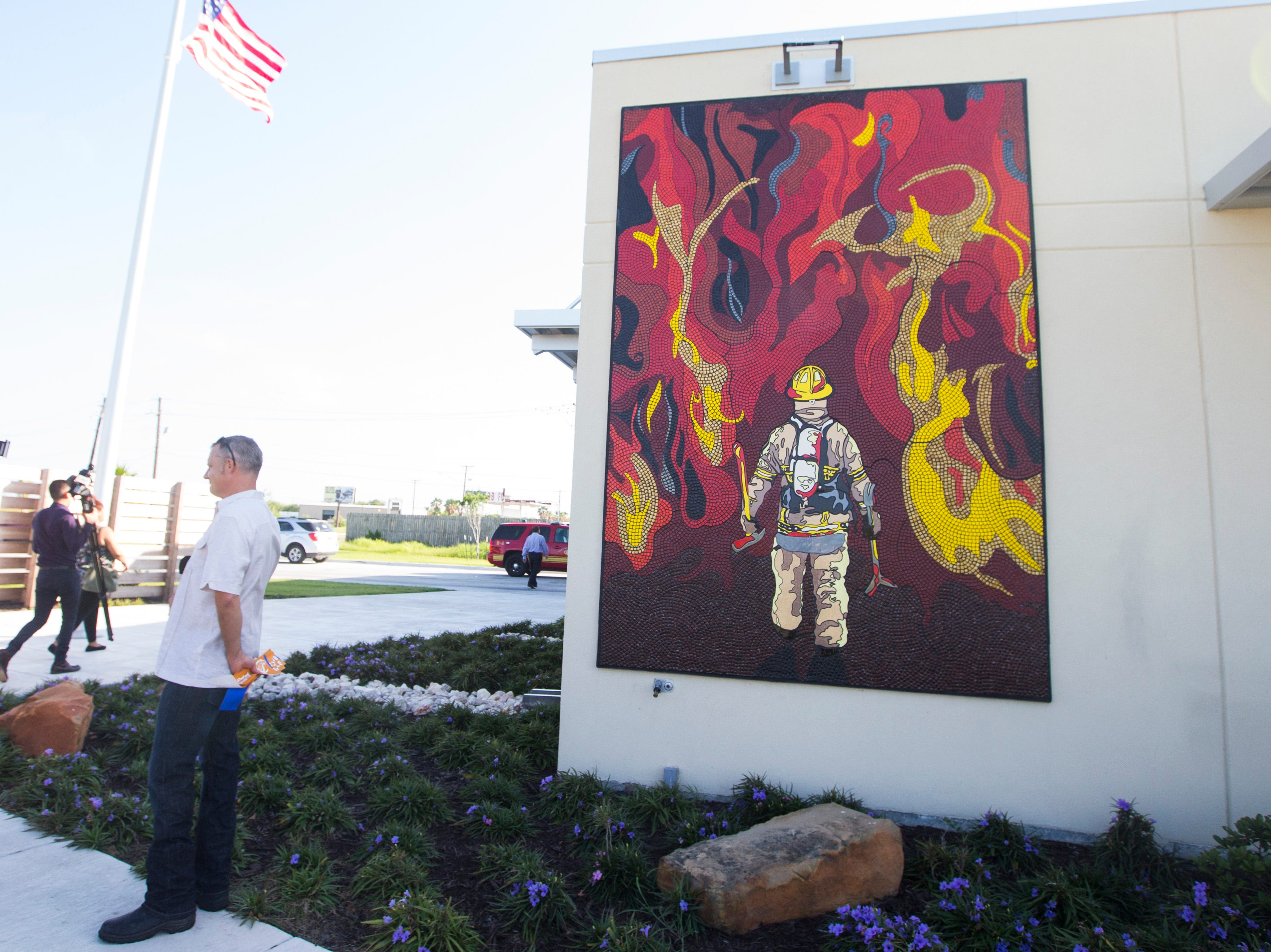 Artist Jerimiah Heye stands in front of his work during a dedication ceremony for his mural Stay Together, Breathe on Monday, July 23, at Fire Station No. 18 in Corpus Christi.