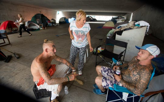 Some of the people living in a homeless camp off third street near the Bengals Stadium will be moved to another temporary location on the east side starting Tuesday. (L-R) Trey, Laura and Bob were unsure where they would be locating next. For the past few months, people who use the breezeway as a cut-through from the parking lot near the Bengals stadium, have complained about the growing homeless encampment.