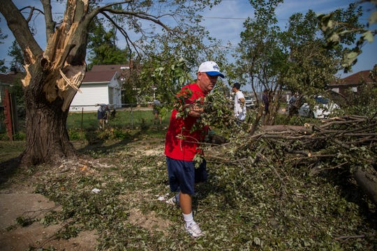 Marshalltown baseball head coach Steven Hanson pulls a branch away from a tree knocked down by a tornado days earlier as he and his players help clean up storm damage on Monday, July 23, 2018, in Marshalltown.