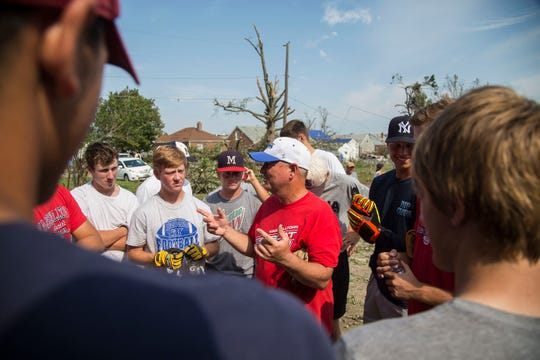 Marshalltown baseball head coach Steven Hanson talks to his team as they finish up clearing a yard of storm damage and discusses which house they'll go to next on Monday, July 23, 2018, in Marshalltown.