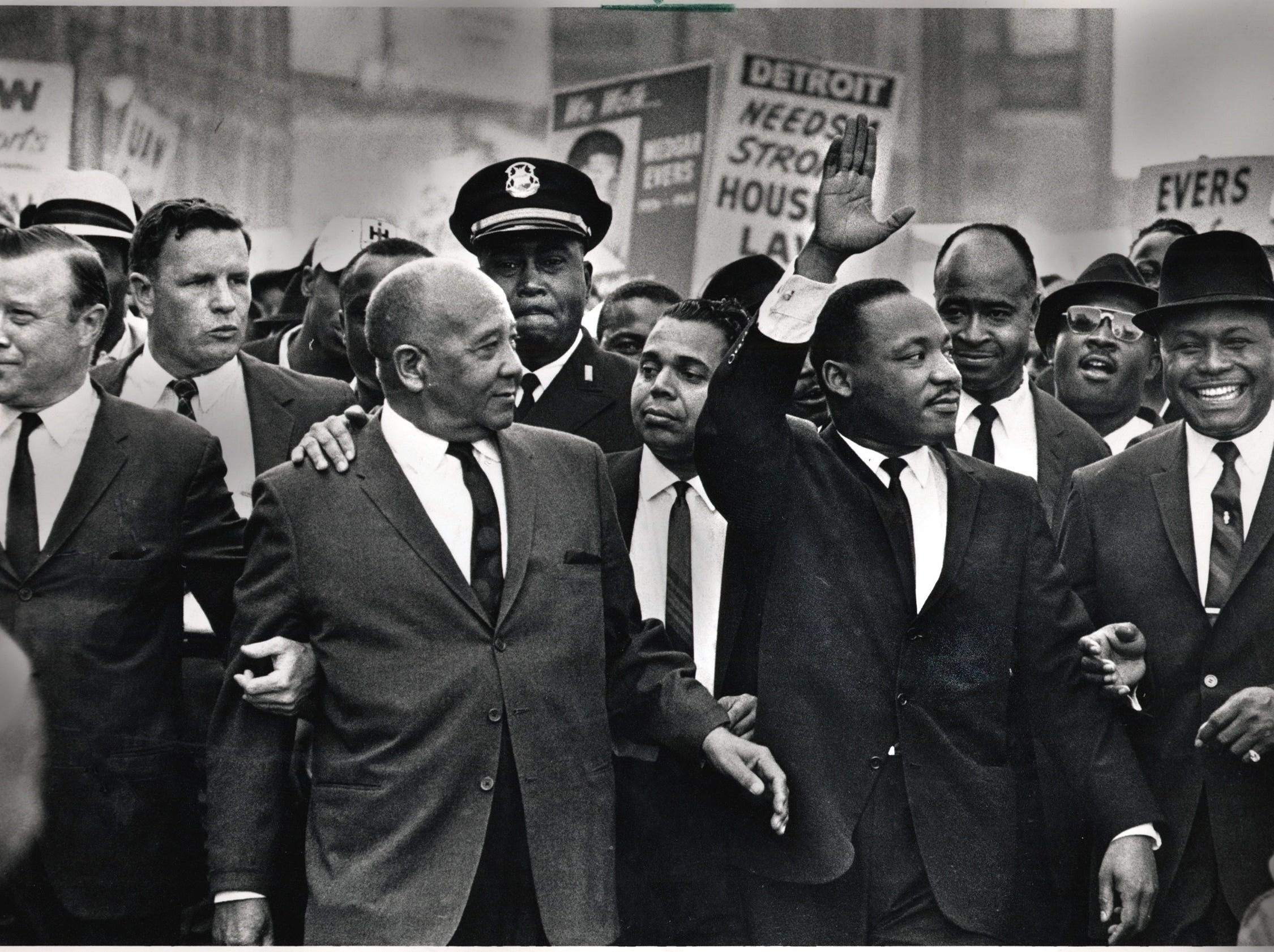 "The Rev. Martin Luther King Jr. waves to onlookers as he leads the 125,000 strong ""Walk to Freedom"" on Woodward Avenue in Detroit  in 1963.  From left to right in the front row are: Walter Reuther, Benjamin McFall, Dr. King, and Rev. C.L. Franklin."