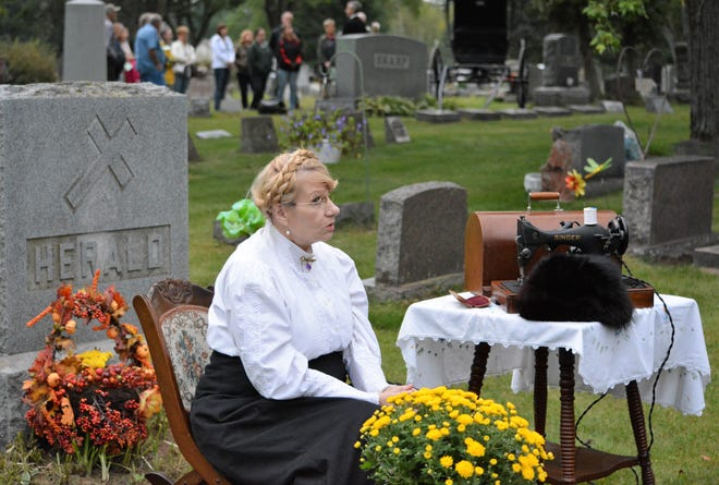 In a file picture from the 2015 cemetery walk in Oconto, Pamela Loberger portrays Clara Herald who worked in the logging camps of northern Oconto County and then became a city resident. (Herald's headstone is at left.)