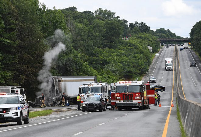 Firefighters spray down the remains of a tractor trailer cab that caught fire at the Grove Road exit on I-185 blocking the southbound lanes Monday, July 23, 2018.