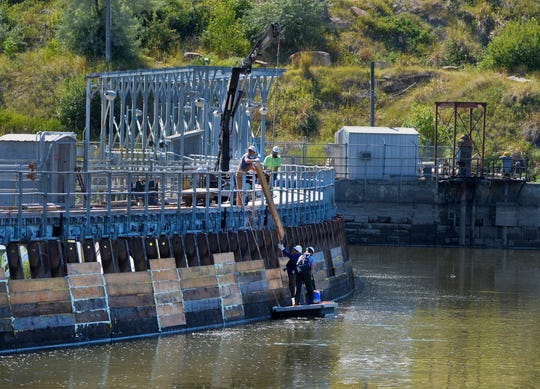 Northwestern Energy dam tenders place new boards on the metal stanchions at the top of Black Eagle Dam on Monday morning.  The boards and stanchions are used to hold water above the dam but can be dropped in sections to let a desired amount of water escape over the top of the dam.