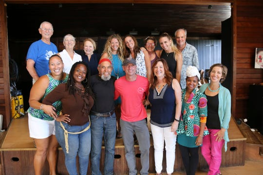 """In this Feb. 28, 2018 photo provided by Jill Trunnell, country singer Kenny Chesney, foreground center, poses with residents, background from left, Jim Furneaux, Carol Furneaux, Glenda Werbel, Angela Warren, Jenna Fox, Jude Woodcock, Jillian Grossman and Bill Stelzer, and foreground from left, Audrey Penn, Ingrid Smith, Eddie Bruce, Chesney, Kim Wild, Jeune Provost and Lauren Magnie at St. John School of the Arts in St. John, U.S. Virgin Islands. After Hurricane Irma decimated the U.S. Virgin Islands last year, Chesney started writing songs and organizing relief efforts. He is donating proceeds from the sale of his new album, """"Songs for the Saints,"""" to a foundation he set up to support recovery on the islands. (Jill Trunnell via AP)"""