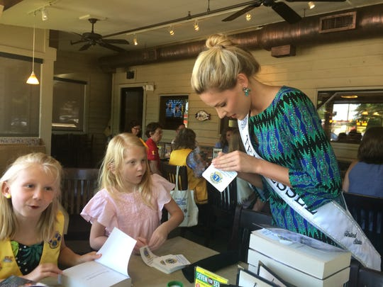 Powell High grad Leslie Truan (right), Miss Tennessee United States, gets dictionaries ready for distribution by the Knox North Lions Club with Adelie Murray (left) and Makady Hill.