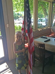 """Lions Club """"Cub"""" Adelie Murray holds the flag for the pledge of allegiance."""