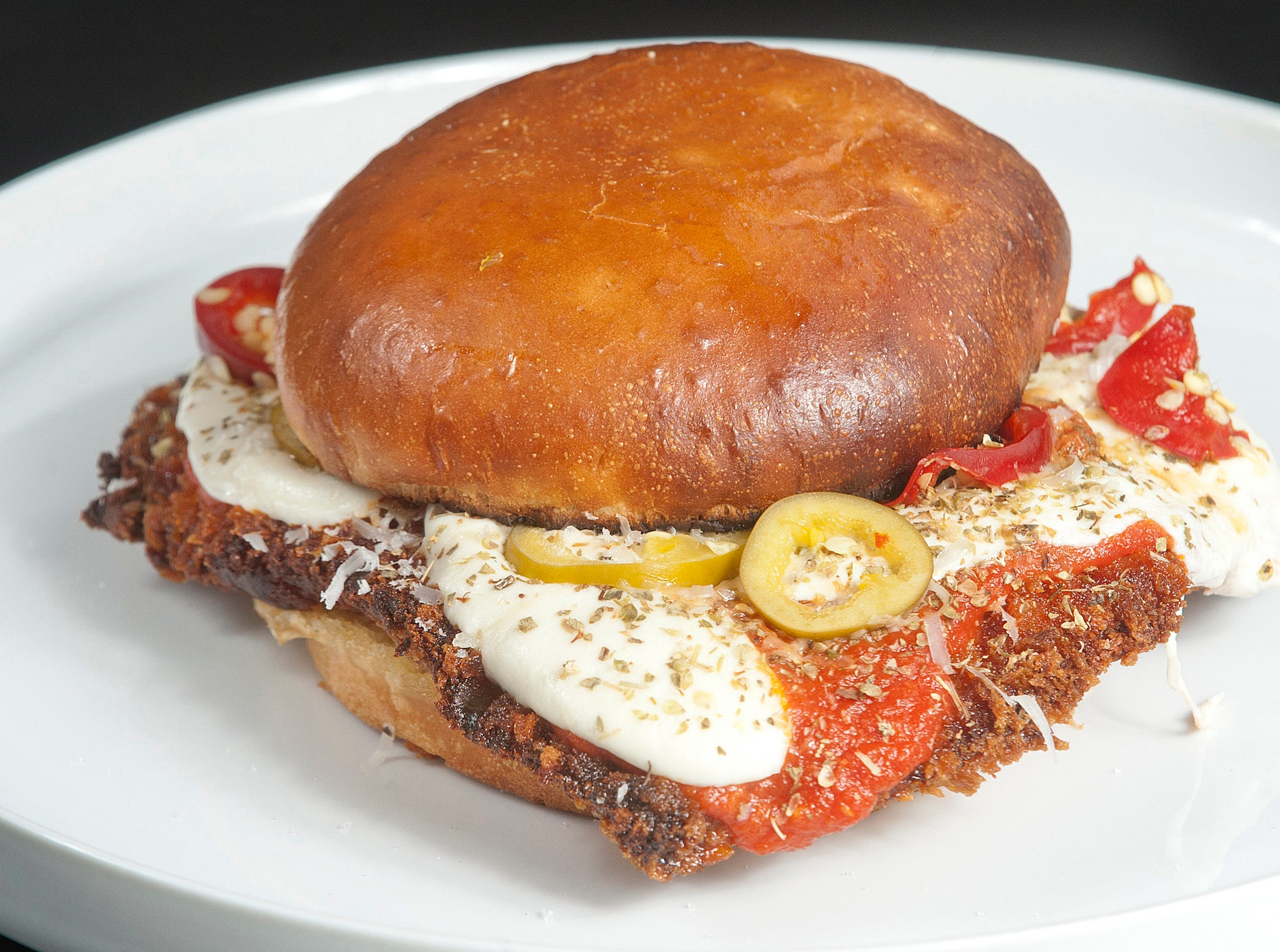 bar Vetti's Crispy Pork Parmesan sandwich is made with a crispy pork loin served on a pretzel bun and topped with tomato sauce, mozzarella and parmesan cheeses and pickled peppers. July 10, 2018