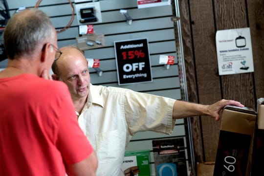 Employee Ralph Roesner, right, helps a customer with information about television antennas on Friday, July 20, 2018, at Clinton Electronics in downtown St. Johns. The business, a RadioShack dealership, is closing its doors after 37 years at the end of August.