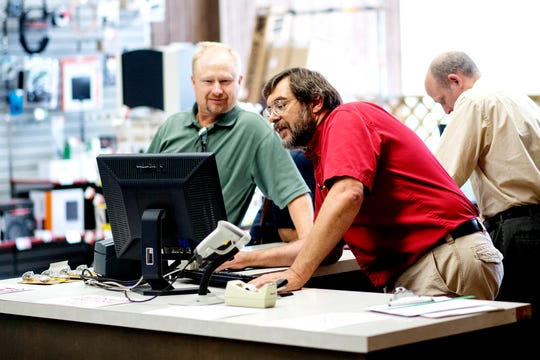 Employee Mike Maiville, right, works with a customer on Friday, July 20, 2018, at Clinton Electronics in downtown St. Johns. The business, a RadioShack dealership, is closing its doors after 37 years at the end of August.