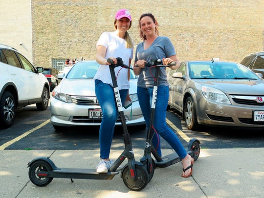 Kirby Bridges, left, and Megan Garlington pose with the Bird scooters they were taking for an afternoon ride in Milwaukee. Milwaukee is suing California-based Bird to stop the company from renting bikes because the city contends they are illegal to operate on streets and sidewalks.