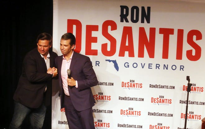Donald Trump Jr., right, greets Florida gubernatorial candidate U.S. Rep. Ron DeSantis at a campaign rally Wednesday, July 18, 2018, in Orlando, Fla.