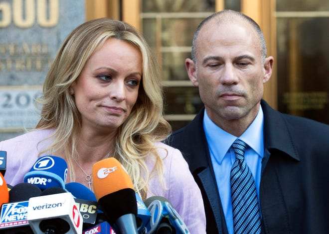 FILE - In this April 16, 2018 file photo, adult film actress Stormy Daniels, left, stands with her lawyer Michael Avenatti as she speaks outside federal court, in New York. Trump's personal attorney wants a federal judge to stop the lawyer for porn actress Daniels from speaking to reporters. An attorney for Michael Cohen filed court papers Thursday night, June 14, 2018, alleging Daniels' lawyer Avenatti is tainting the case. (AP Photo/Mary Altaffer, File)