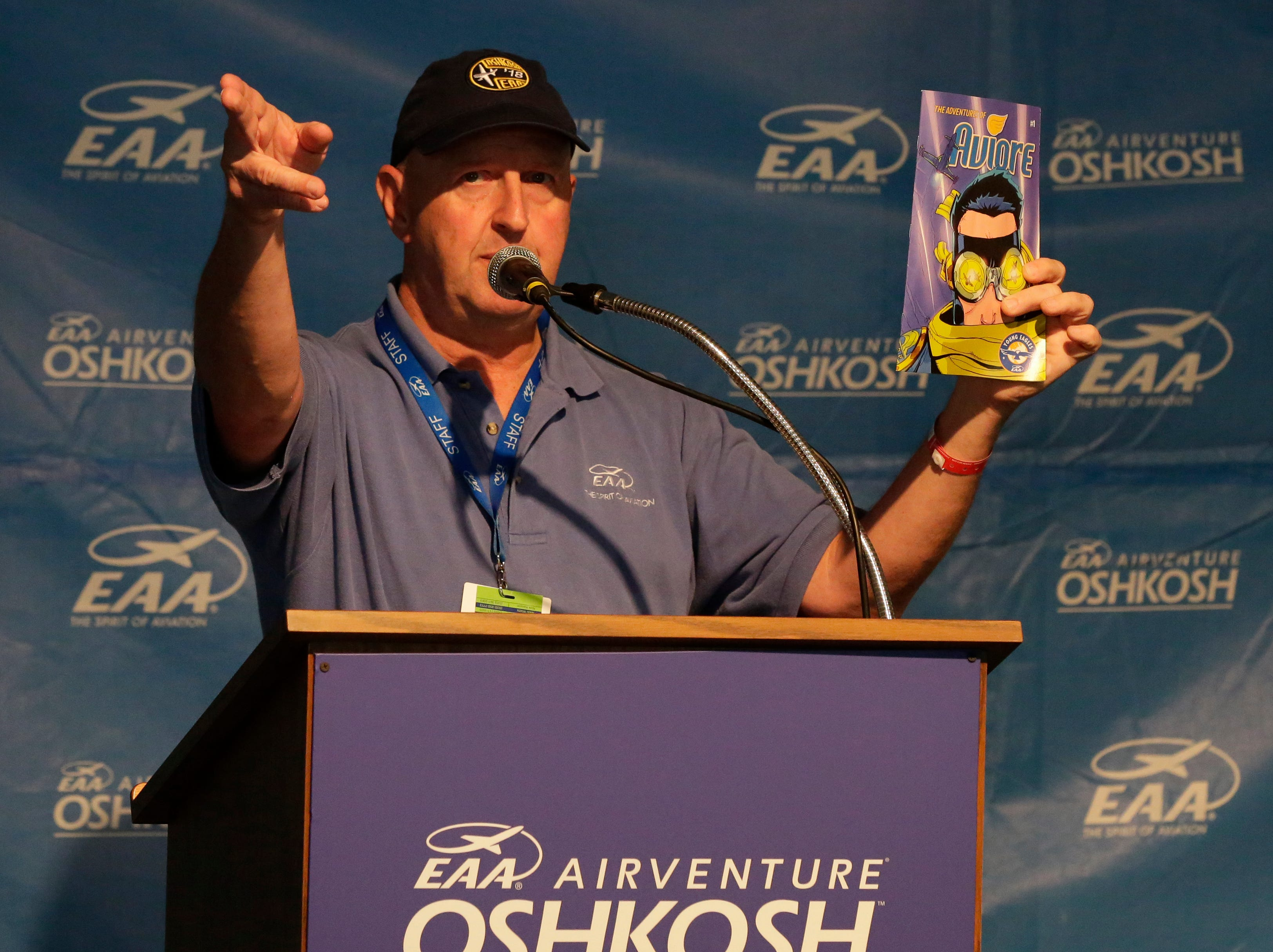 Dick Knapinski, Experimental Aircraft Association Public Relations Director hold a morning briefing and shows off the latest from comic book writer Stan Lee the new super hero of EAA is Aviore.  The first day of AirVenture 2018 opened on July 23, 2018.  Thousands of people will pass through the gates of AirVenture. Joe Sienkiewicz/USA Today NETWORK-Wisconsin